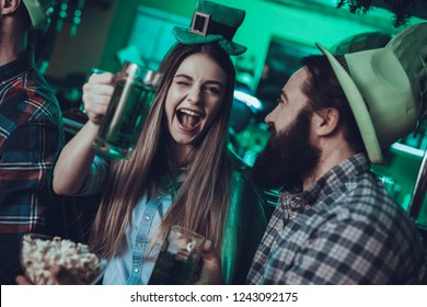 Saint Patrick's Day Party. Friends is Celebrating. Happy People is Drinking a Green Beer and Eating a Popcorn. Friends is Men and Woman. Woman is Winking. People Wearing a Green Hats. Pub Interior.