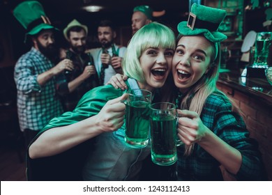 Saint Patrick's Day Party. Group of Friends is Celebrating. Happy People is Drinks a Green Beer. Friends is Young Men and Women. Women Toast with Each Other. People Wearing a Green Hats. Pub Interior.