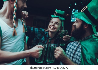 Saint Patrick's Day Party. Group of Friends is Celebrating. People is Drinking a Green Beer. Friends is Young Men and Woman. Happy Men Toast with Each Other. People Wearing a Green Hats. Pub Interior.