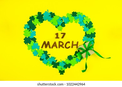 "Saint Patrick's Day. Wooden letters ""17 march"" lying on yellow background in heart shape of green three petal clovers and gift box"