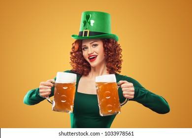 Saint Patricks Day. Young ginger Oktoberfest leprechaun, wearing grenn dress and hat, serving big beer mugs on orange background..