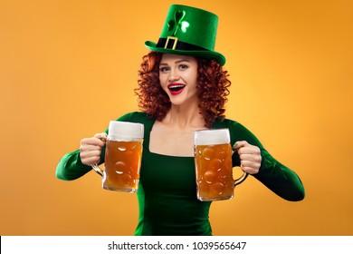 Saint Patricks Day. Young ginger Oktoberfest leprechaun, wearing green dress and hat, serving big beer mugs on orange background..