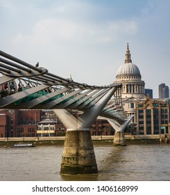 Saint Paul Cathedral with Millenium Bridge over River Thames and People walking in London,England,UK-April 2019