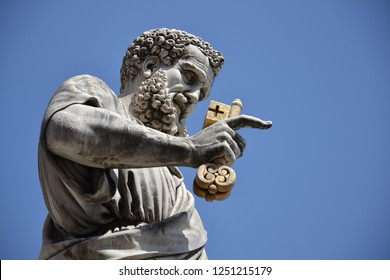 Saint Peter holding golden key to heaven statue sculpted by Giuseppe De Fabris at St. Peters Square in Vatican City, Rome, Italy, low angle view, blue clear sky background on sunny summer day