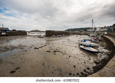 SAINT PETER PORT, GUERNSEY, UNITED KINGDOM - AUGUST 20, 2016 : Ships and sailboats lies on the seafloor at low tide.