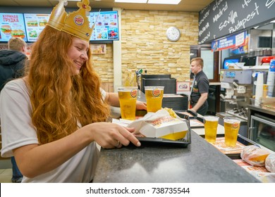 SAINT PETERSBURG - CIRCA OCTOBER, 2017: woman with a cardboard crown at Burger King restaurant. Burger King is an American global chain of hamburger fast food restaurants.