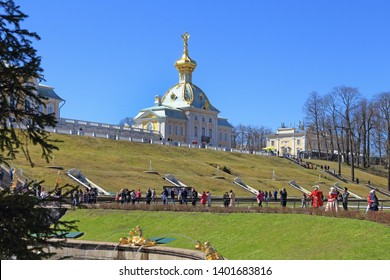 "Saint Petersburg, Peterhof, RUSSIA — MAY 03, 2017: Tourists walk on the background of the View from the Western wing of Petrodvorets ""Housing under the Arms"" in Peterhof"