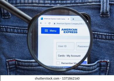 Saint Petersburg, RUSSIA - 09 April, 2019: American Express website homepage. American Express logo visible on on the smartphone display. Company name is approached through a magnifying glass.