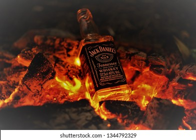Saint Petersburg, Saint Petersburg / Russia - 09 September 2017: Bottle of whiskey Jack Daniel's on fire with burning charcoals in the night
