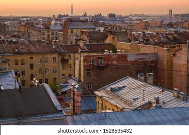 "Saint Petersburg, Russia - 09.09.2019: View of the historic part of city from the ""Loft progect Etagi"". Roofs of Petersburg, Ligovsky prospekt. Sunset sky. Lakhta center on the horizon."