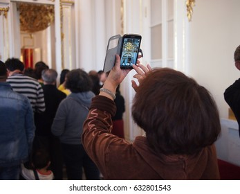Saint Petersburg, Russia - 15 September, 2016: A Chinese tourist takes a photo on her mobile phone inside the Hermitage Museum
