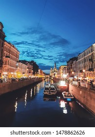 Saint Petersburg, Russia - August 14, 2019: The Griboyedov Canal embankment w Church of the Savior on Spilled Blood w dark sunset blue sky & water, summer evening in city historical cultural center