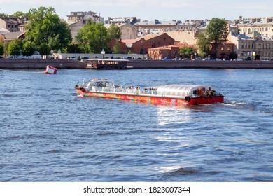 Saint Petersburg, Russia - August 14, 2020: City red sightseeing boat «Hop on Hop off» on Neva river in Saint Petersburg.