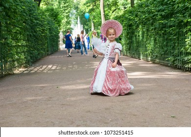 SAINT PETERSBURG, RUSSIA - AUGUST 18, 2017: Little girl in 1800's dress with fan for a walk in Summer Park. This park is one of the oldest in Saint Petersburg, it was designed by Czar Peter in 1704.