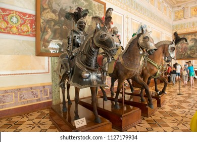 SAINT PETERSBURG, RUSSIA - AUGUST 18, 2017: Mannequins of ancient knights in armor on horses in Hermitage museum with murals on background. Riding, hero, medieval warriors, historic landmarks, castle.