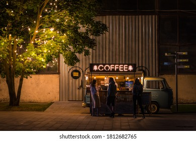 Saint Petersburg, Russia - August 18, 2020: a group of young people stand in front of a street coffee shop equipped in a retro van in Sevkabel Port.