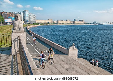 SAINT - PETERSBURG, RUSSIA - AUGUST 19, 2017: People ride bicycles next to the sculptures of sphinxes on Sverdlovskaya Embankment near The Neva River