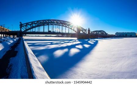 Saint Petersburg. Russia. The Bridge of Peter the Great. St. Petersburg on a winter day. Bolsheokhtinsky bridge. Sunrise over the frozen Neva. Traveling in Russia. Skyline of St. Petersburg.