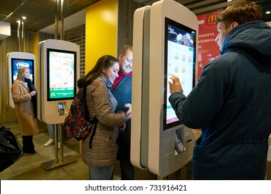 SAINT PETERSBURG, RUSSIA - CIRCA OCTOBER, 2017: people use ordering kiosks at McDonald's restaurant. McDonald's is an American hamburger and fast food restaurant chain.
