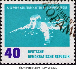 Saint Petersburg, Russia - December 19, 2019: Postage stamp issued in the German Democratic Republic with the image of a breaststroke swimmer, circa 1962.