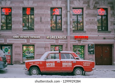 SAINT PETERSBURG, RUSSIA - JANUARY 02 , 2018 : The first in Russia Museum of Soviet Lifestyle  and a an old, red , covered with a snow, promotional carin front of its entrance.