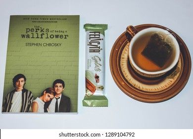 Saint Petersburg, Russia - January 14, 2019: The Perks of Being a Wallflower book by Stephen Chbosky; chocolate FELICITA Cioccolato by russian company; and cup of tea. Illustrative editorial image