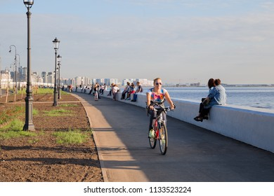 SAINT PETERSBURG, RUSSIA - JULY 11, 2018: People are resting on a summer evening on new embankment of the Gulf of Finland on Krestovsky Island