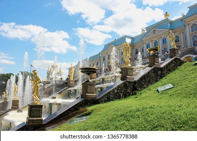 Saint Petersburg, Russia - July 13, 2018: Sculptures of The Grand Cascade fountain in Peterhof Palace under the summer sunny blue sky among green trees and splashes of water