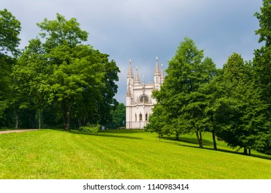 Saint Petersburg, Russia, june 2017. Gothic Chapel among lush green trees during summer with lawn at foreground  in Alexandria Park in Petergof