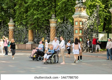 SAINT PETERSBURG, RUSSIA - JUNE 25, 2019: Tourists in wheelchairs at the fence of the Mikhailovsky garden look at the Church of the Savior on Blood. Saint Petersburg, Russia