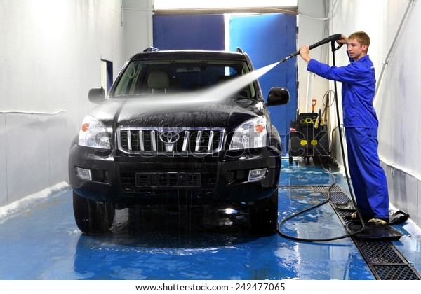 Saint Petersburg, Russia - June 26, 2014: Car maintenance,  car service, manual car washing, Worker at Car Wash Shop,  Using Pressure Washers on Cars,  man washing car with compression water