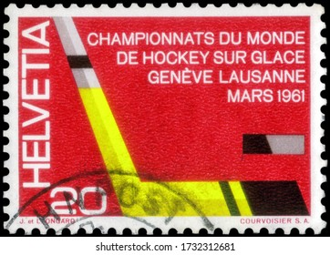 Saint Petersburg, Russia - May 05, 2020: Postage stamp issued in the Switzerland with the image of the Ice Hockey Stick and Puck. From the series on World Championships Ice-hockey, circa 1961