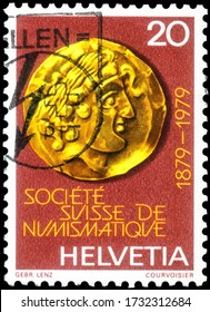 Saint Petersburg, Russia - May 05, 2020: Postage stamp issued in the Switzerland with the image of the Golden quarter Stater with Apollo Head. Centenary of Swiss Numismatic Society, circa 1979