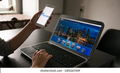 SAINT PETERSBURG, RUSSIA - MAY 14, 2019: user of the site and application. Website and logo of the Russian company gazprom on the screens of gadgets. Cross platform services. Illustrative editorial