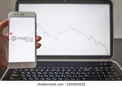 SAINT PETERSBURG, RUSSIA - MAY 14, 2019: logo of the Russian company mail.ru group on the smartphone screen on the background of stock charts. Investments in Russian business, illustrative editorial