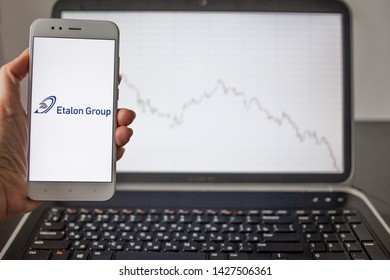 SAINT PETERSBURG, RUSSIA - MAY 14, 2019: logo of the Russian company Etalon group on the smartphone screen on the background of stock charts. Investments in Russian business, illustrative editorial