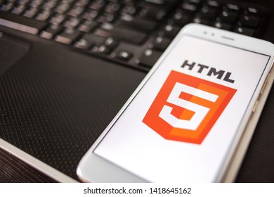 SAINT PETERSBURG, RUSSIA - MAY 16, 2019: HTML5 Programming language for mobile development, concept. Smartphone on the laptop keyboard, the programmer's workplace. illustrative editorial