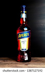Saint Petersburg, Russia - May, 2019: Bottle of Aperol aperitif wine on wooden table, black background. Closeup of bottle label. Copy space