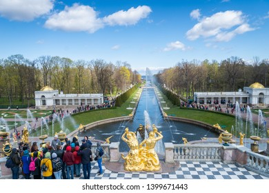 Saint Petersburg, Russia - May 2019: Peterhof fountains and palace view and tourists visiting the Lower Park. The Peterhof Palace is a series of palaces and gardens and a popular tourist sight.