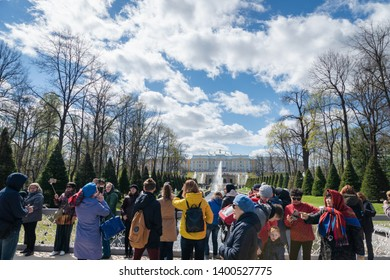 Saint Petersburg, Russia - May 2019: Peterhof fountains and palace view and tourists visiting the Lower Park. The Peterhof Palace is a series of palaces and gardens and a popular tourist sight