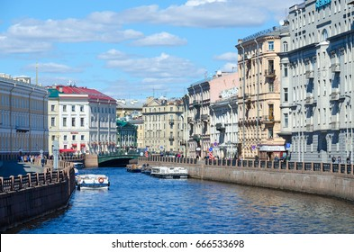 SAINT PETERSBURG, RUSSIA - MAY 3, 2017: Excursion boats on Moika River near Green Bridge. Unknown people walk along street, St. Petersburg, Russia