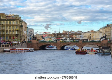 SAINT PETERSBURG, RUSSIA - MAY 3, 2017: Unknown tourists are on excursion boats on Fontanka River near Anichkov Bridge, St. Petersburg, Russia