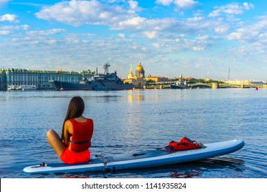 Saint Petersburg. Russia. Morning in Petersburg. The girl is looking at warships. The Neva River in St. Petersburg. A warship in the background of the city. Warships in St. Petersburg.