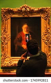 Saint Petersburg, RUSSIA November 13, 2019 : Tourist listen to audio guide and taking picture by smart phone in gallery of Rembrandt hall of The State Hermitage Museum in Saint Petersburg, Russia.