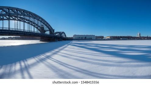 Saint Petersburg. Russia. Peter the Great Bridge. Bolsheokhtinsky bridge. Snow in St. Petersburg. Bridge casts a shadow. Bolsheokhtinsky Bridgework on the background of blue sky. Neva. Cities Russia