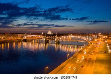 Saint Petersburg. Russia. Rivers Of St. Petersburg. Bridges Of St. Petersburg. White night. Bolsheokhtinsky bridge against the blue sky. Peter The Great Bridge. Smolny cathedral.