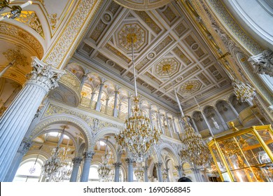 Saint Petersburg, Russia - September 12 2019: The ornate white and gold ceiling, walls and chandelier inside the Pavilion Hall of the State Hermitage museum in St Petersburg, Russia.
