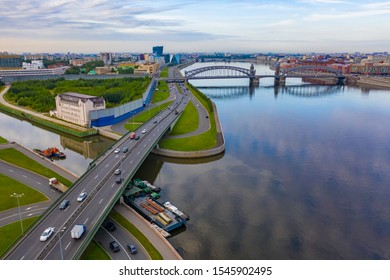 Saint Petersburg. Russia. View of St. Petersburg from a height. Rivers Of St. Petersburg. The River Neva. Ships are moored near the shore. Peter The Great Bridge. Bolsheokhtinsky bridge.
