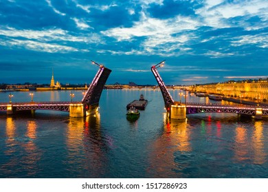 Saint Petersburg. White night. Bridges Of St. Petersburg. Rivers Of St. Petersburg. Divorced Palace bridge. Under the bridge is a barge. Tugboat pulls the barge. Navigation. Water transport. Russia