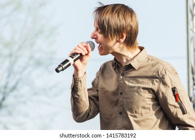 Saint Petersburg/Russia - 4 27 2019: A young, expressive blond man shouts into a microphone. The vocalist of a rock band sings on stage during an open air concert. Professional musician, front man.
